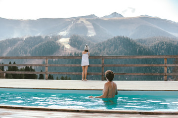 Family spending vacation in swimming pool with mountain landscape