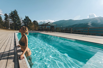 Young woman spending vacation in swimming pool with mountain landscape