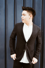 Portrait of young Asian business man wearing black suit