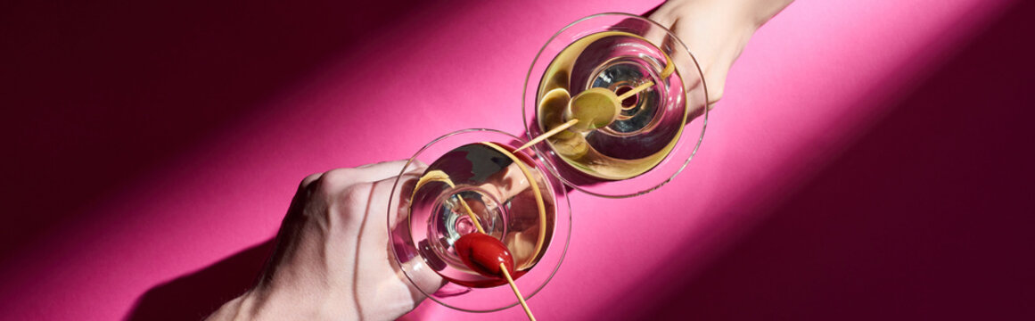 Cropped view of man and woman holding martini cocktails on pink background, panoramic shot