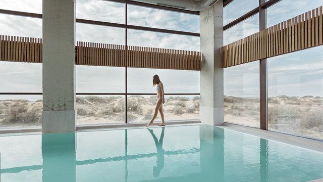Girl relaxing in luxury swimming pool in modern hotel