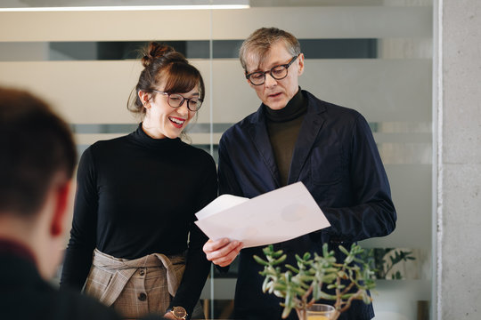 Middle aged businessman and young female assistant working during office meeting. Two architect colleagues planning new project in office.
