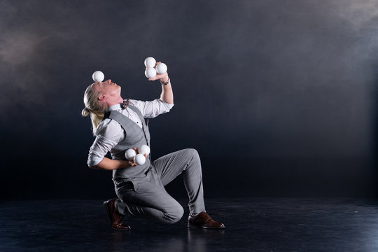 Juggler wearing a suit like a businessman with white balls. concept of success and management