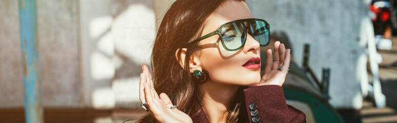 fashionable woman posing in trendy burgundy suit and sunglasses on urban roof