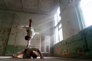 Male duo making acrobatic tricks wearing costume of insane people in abandoned room with sun rays from windows