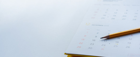 close up side view on yellow pencil over white  calendar schedule background to make appointment...