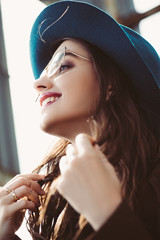 happy stylish girl posing in eyeglasses and hat on urban roof