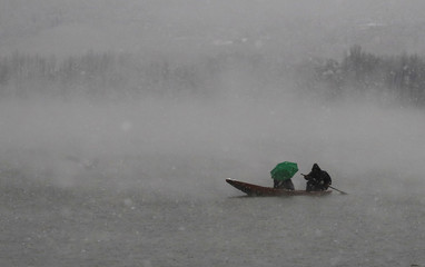 A man rows a boat on the Dal Lake as another holds an umbrella during the season's first snowfall in Srinagar