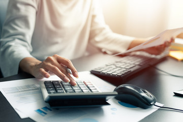 Woman accountant or banker use calculator and computer on table at office