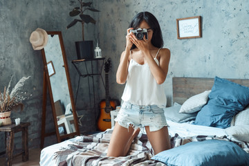 Weekend ar home. Young woman standing on bed taking photo on camera concentrated