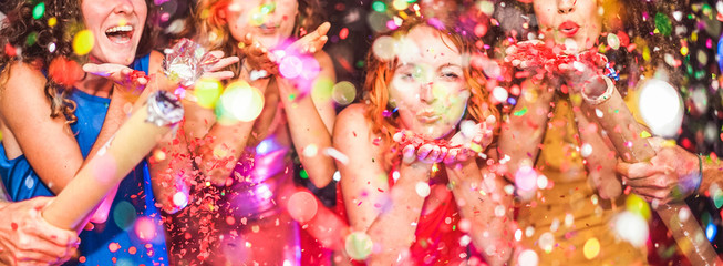 Young friends having party throwing confetti - Young people celebrating on weekend night - Entertainment, fun, new year's eve, nightlife, holidays, concept - Focus on red hair girl hands Wall mural