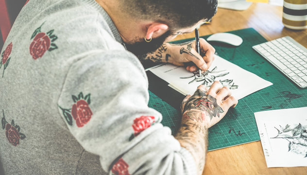 Young tattoo artist drawing sketch inside ink studio - Hipster tattoer at work - Contemporary skin trends generation - Focus on man right hand