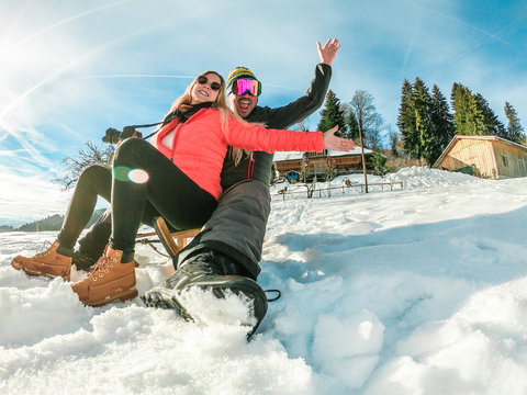 Happy crazy couple having fun with wood vintage sledding on snow high mountains - Young influencers people enoying winter vacation - Travel, love and holiday concept - Focus on faces