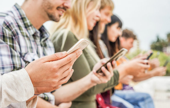 Group of friends watching smart mobile phones - Teenagers addiction to new technology trends - Concept of youth, tech, social and friendship - Focus on close-up phone, hand