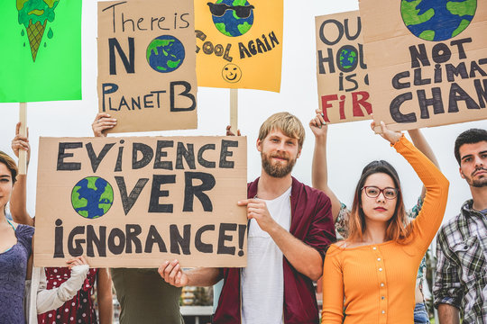 Group of demonstrators on road, young people from different culture and race fight for climate change - Global warming and enviroment concept - Focus on guys faces