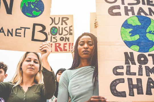 Group of demonstrators on road, young people from different culture and race fight for climate change - Global warming and enviroment concept - Focus on african girl face
