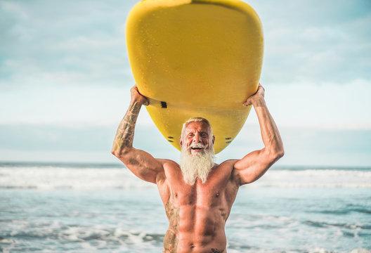 Senior trendy man doing surf with longboard - Happy old guy having fun doing extreme sport - Joyful elderly concept - Focus on his face