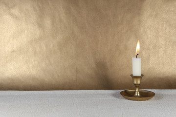 Burning candle in vintage metal candlestick on white table and copy space on dark golden paper background..