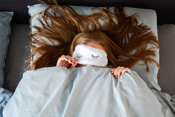 Young woman with long hair and a red manicure is sleeping in bed with sleep mask and peeking from underneath the sleeping mask