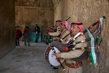 Members of a traditional Jordanian musical troupe perform as they welcome tourists during their visit to Jerash