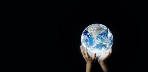 Hand holding blue planet earth globe in dark light. (Elements of this image furnished by NASA.)