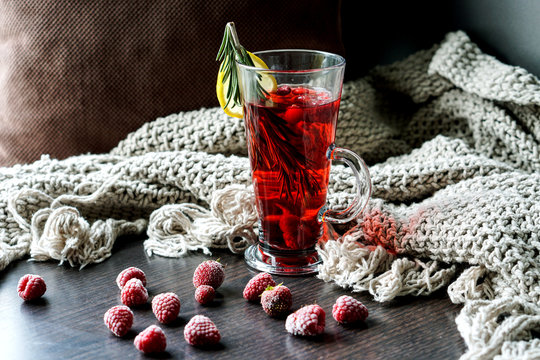 Glass of red fruit tea with lemon and rosemary. Frozen berries. Home