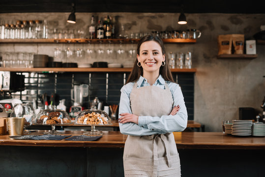 smiling barista in apron standing with crossed arms near bar counter