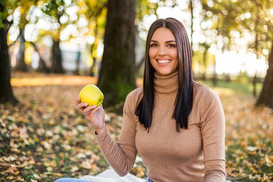 Beautiful woman eating apple while enjoys in autumn and resting in the park
