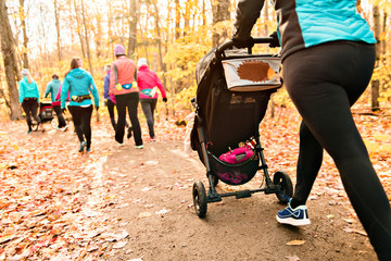 Stroller woman group out running together in an autumn park they run a race or train in a healthy outdoors lifestyle concept