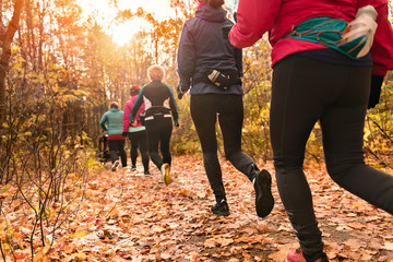 woman group out running together in an autumn park they run a race or train in a healthy outdoors...