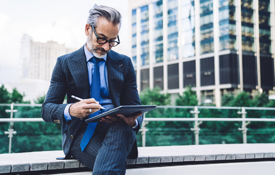 Adult male in business suit drawing on tablet on New York street