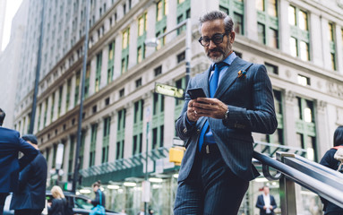 Middle aged businessman typing on smartphone in New York