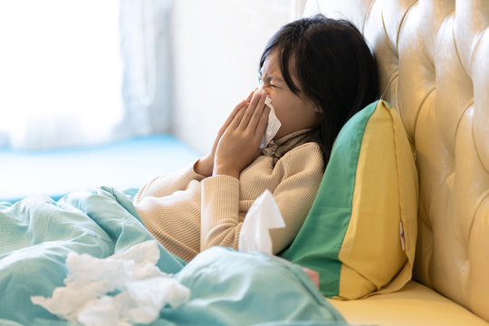 Sick child girl have a cold,blowing nose in paper handkerchief in bedroom,flu or the weather is changing,asian female teenage sneezing in a tissue,concept of allergic rhinitis,hay fever,health care