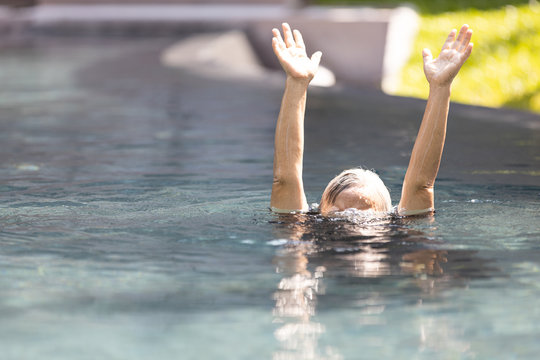Asian senior people struggling underwater, hand peeking out of the water, female drowned in swimming pool, drowning elderly woman in swimming pool asking for help in dangerous situation