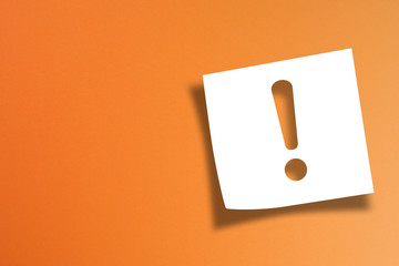 Note paper with exclamation mark on orange background