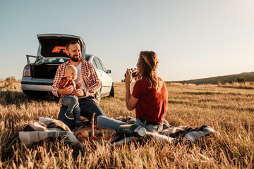 Happy Young Family Mom and Dad with Their Little Son Enjoying Summer Weekend Picnic Sitting on the Plaid Near the Car Outside the City in the Field at Sunny Day Sunset, Vacation and Road Trip Concept