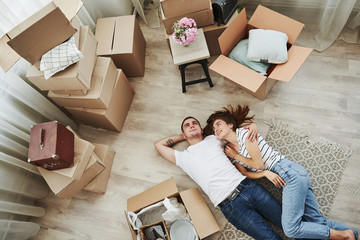 Taking a rest. Lying down on the floor. Cheerful young couple in their new apartment. Conception of moving