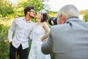 Wedding photographer photographs newlyweds kissing