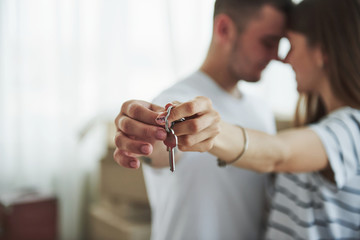 Image focus technique. House keys. Cheerful young couple in their new apartment. Conception of moving