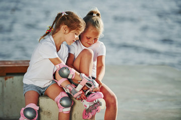 Two little girls with roller skates outdoors near the lake at background