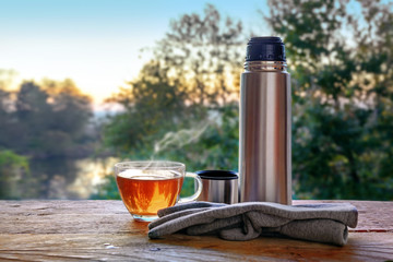Break with hot tea at a trip in the nature, glass cup, thermos jug and gloves on a rustic wooden table in front of a blurred landscape, copy space
