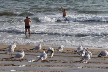 Men take pictures on a beach in Yevpatoriya