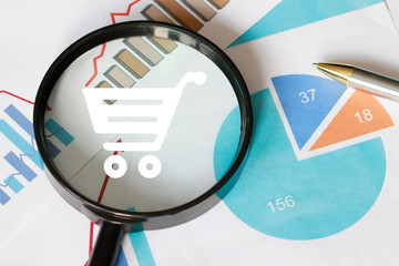 Businessman search on a chart of shopping statistics. Virtual shopping icon on a chart background.