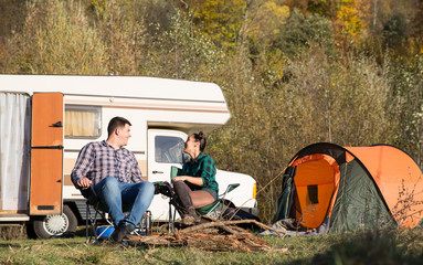 Tuinposter Kamperen Happy couple in autumn relaxing tegether in a campsite