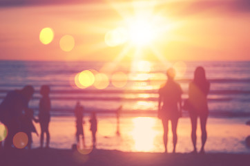 Wall Murals Blur people relax on tropical sunset beach with bokeh sun light wave abstract background.