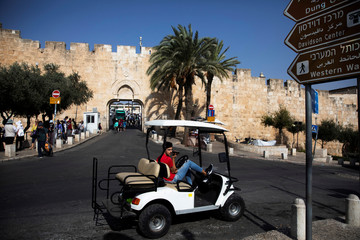 A man look on as he sits in a golf cart near Dung Gate, close to the Western Wall in Jerusalem's Old City