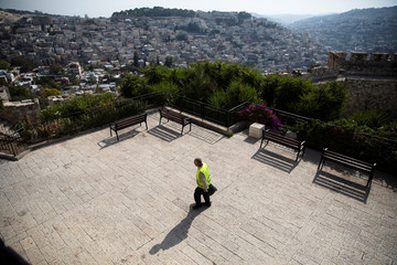 A labourer walks on a lookout point as the Palestinian neighborhood of Silwan is seen in the background, in Jerusalem's Old City