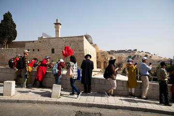 An ultra-Orthodox Jewish man and tourists stand at a point overlooking an area leading to the Western Wall, as part of the al-Aqsa mosque is seen in the background, in Jerusalem's Old City