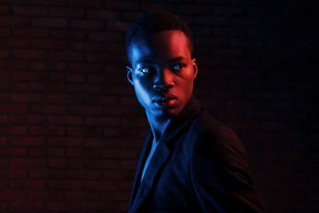 Futuristic neon lighting. Young african american man in the studio