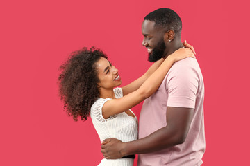 Portrait of happy African-American couple on color background